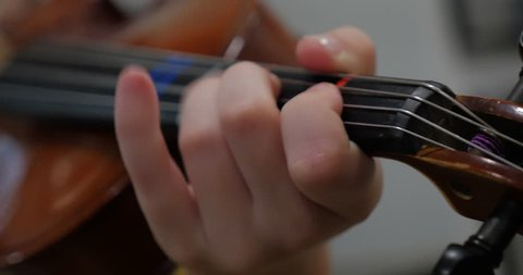 Close up of a young boy's fingers playing a violin