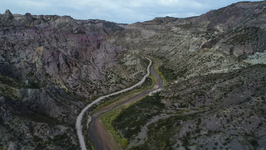 Aerial drone scene of Atuel river canyon in San Rafael, Mendoza, Cuyo Argentina. Camera moving upwards and modern new 4x4 van appears. Gravel street next trees and river. Colorfull rocks. | Shutterstock HD Video #1013019467
