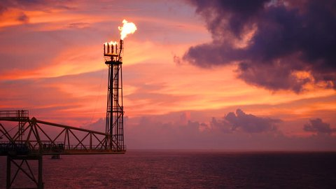 footage of oil and gas platform with flare burning bridge with sun rise and beautiful clouds in the morning for oil and gas industry concept.