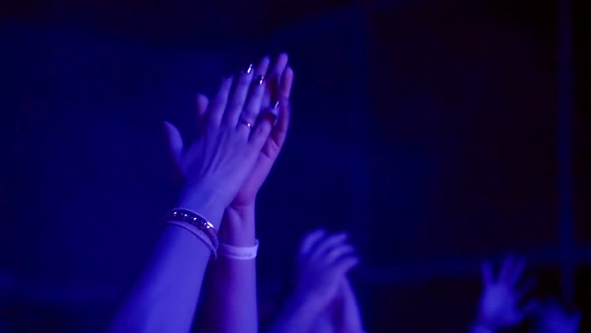people in audience on a gig are applauding, close-up of hands of joyful woman, cheering rhythmically