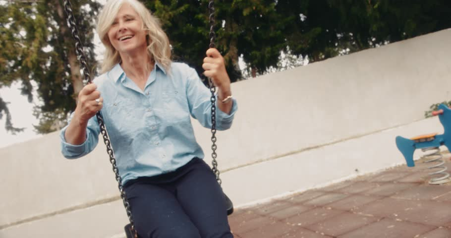 Happy active retired senior woman having fun at playground sitting on swing in spring