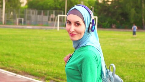 Attractive sporty muslim girl in hijab walks around the stadium and smiles at the camera,slow mo