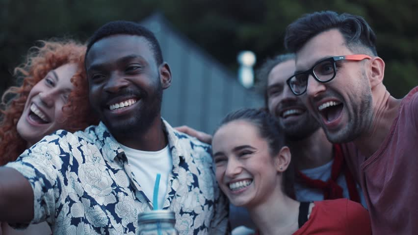 Group of friendly young people taking selfie outdoors, smiling. Students celebrating the final of studying in country house, having fun. Evening. Multicultural.   Shutterstock HD Video #1013038427
