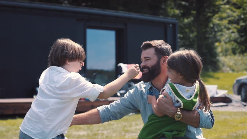 Happy Caucasian children running to meet dad. Little boy and girl hugging daddy. Father coming home. Country house. Daytime. Outside. Best moments.   Shutterstock HD Video #1013038997