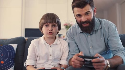 Attractive man in business clothes playing videogame with little guy. Handsome man with beard using joysticks, giving five. Win. Father hugging son. Home.