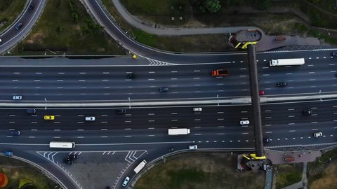 Aerial view of a motorway. Camera move left with a view on car interchange. A lot of cars ride on the 10 lanes motorway.