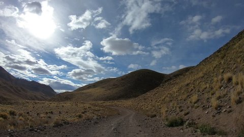 Timelapse scene of gravel street. Camera griped to a car going from hot springs of Cajon Grande, to Las Loicas town, Mendoza, Argentina. Grasslands steppe landscape with mountains and clouds.