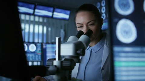 Female Medical Research Scientist Looking Through the Microscope Types Acquired Data in the Computer. Laboratory.  Shot on RED EPIC-W 8K Helium Cinema Camera.