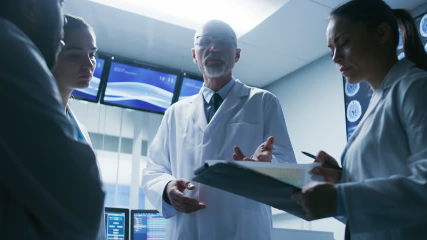 Low Angle Shot of the Meeting of the Team of Medical Scientists in the Brain Research Laboratory. Neurologists / Neuroscientists Having Analytical Discussion. Shot on RED EPIC-W 8K Helium Camera