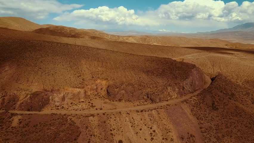 Aerial drone shot pans to follow the railroad tracks leading up to the Polvorilla Viaduct in Argentina