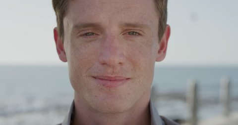 close up portrait handsome young red head man smiling happy student enjoying successful lifestyle relaxing on warm summer day seaside slow motion ginger freckles