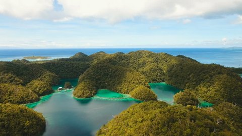 Aerial view: beach, tropical island, sea bay and lagoon, Siargao. Tropical landscape hill, clouds and mountains rocks with rainforest. Azure water of lagoon. Shore Landscape Bay. Aerial video.Seascape