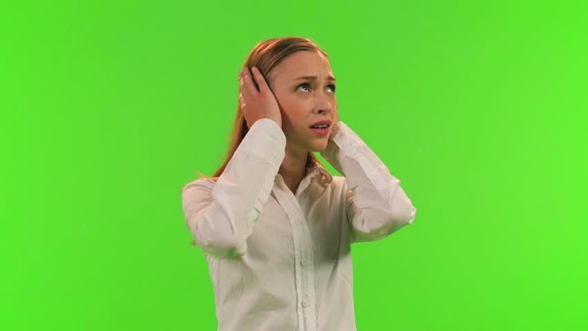 A disturbed woman puts an earmuffs to protect her ears from noise, relaxes and smiles, over a green screen.