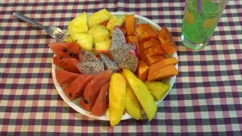 On the table is a plate of fruit. A woman's hand takes a pityahya with a fork