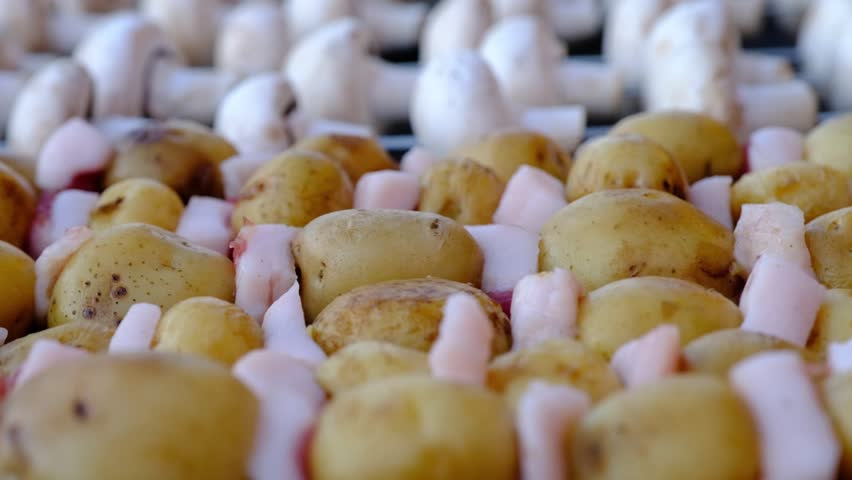 A view of fresh potatoes and lard on skewers and mushrooms on a background, ready to be cooked. Street food.