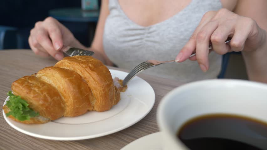 an unrecognizable woman with a beautiful neckline, breakfasts in a cafe with a croissant sandwich with boiled pork and drinking coffee. 4k, slow-motion, close-up.