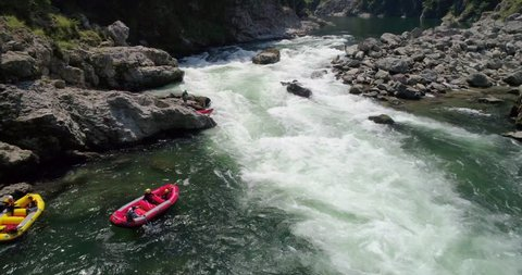 Aerial shot as raft capsizes in the whitewater on the Yoshino River in Tokushima Japan 60fps for slow motion