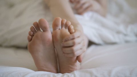 Woman applying cosmetic foot cream, doing feet massage, close up.