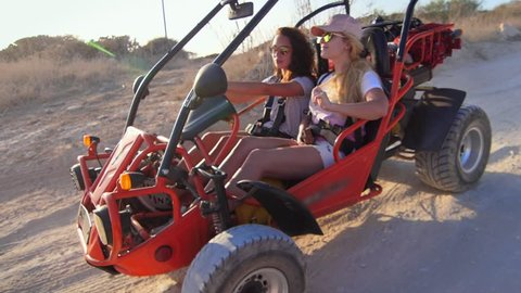 Female driver ride on buggy car. Enjoy extreme riding. Tourists driving dune buggy. Extreme holiday. Women drive on sand buggy car. Girl driving dune transport
