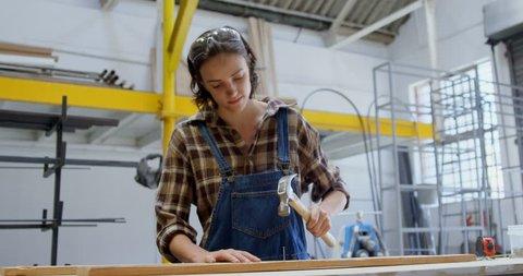 Female welder hammering nail on a wooden plank in workshop 4k