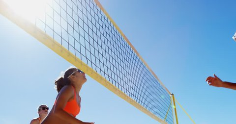 Female volleyball players playing volleyball at beach 4k