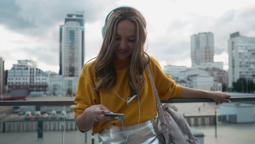 Portrait of young cute attractive young girl in urban city streets background listening to music with headphones. Woman wearing yellow blouse and silver skirt. | Shutterstock HD Video #1013167247