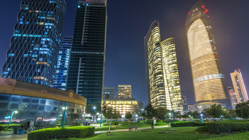 Skyscrapers in Abu Dhabi Skyline at night timelapse hyperlapse, United Arab Emirates. View from Corniche with illuminated modern towers