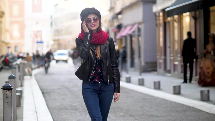 Attractive woman in black cap and sunglasses on city street sending air kiss