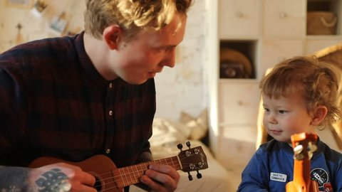 Tattooed happy man showing charming infant son how to play ukulele sitting in sunlight.
