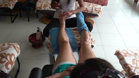 Thai foot massage. The masseuse uses a teak wand for foot reflexology