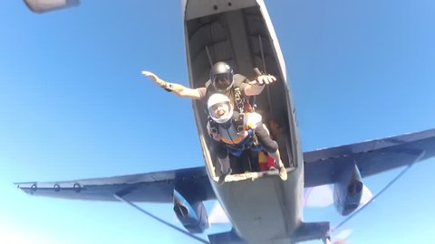 Skydiving. Tandem is jumping out of a plane and two friends are flying to the one.