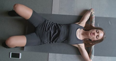 young tattooed woman doing crunches exercise stretching during fitness sport workout at home. top view .Living room domestic training. 4k slow motion video