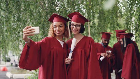 Pretty female graduates are taking selfie with diploma scroll using smartphone, young women are posing with other students moving and talking in background.