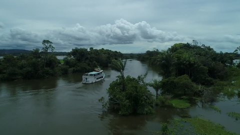 Piranha fishing excursion on a junk boat in the Amazon river near Santarem, Brazil. Tracking shot through trees, following with drone behind boat.
