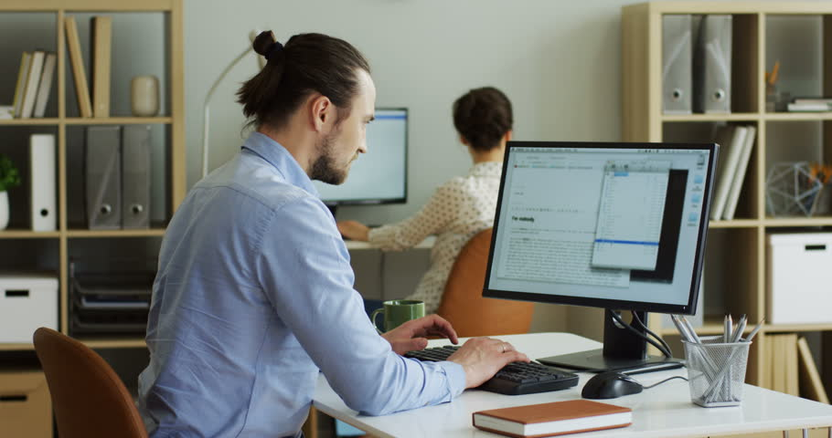 Rear of the male nervous Caucasian office worker typing and texting on the laptop computer while it being broken and has error writing on the screen. Indoors.   Shutterstock HD Video #1013276147