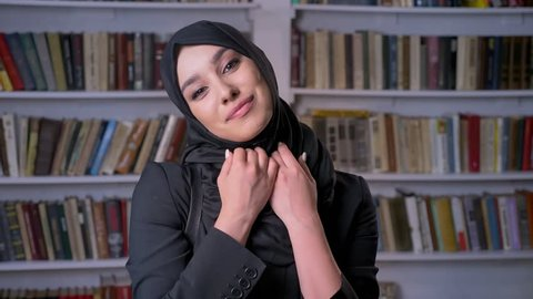 Young beautiful muslim girl in hijab crosses arms, watching at camera, religious concept, bookshelf on background