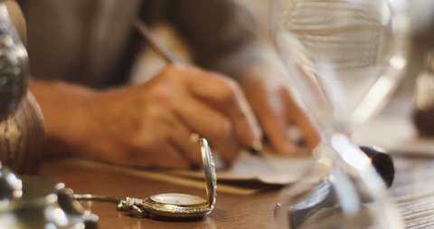 Close up of the different old things lying on the wooden table and blurred old male hands writing a letter with ink on the background.