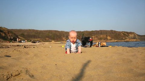 young father and child playing with sand on the beach. Russia, the Sea of Japan