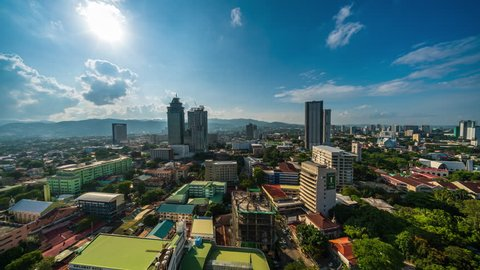 Cebu City, Philippines - June 7, 2018: Cebu City Timelapse view showing view over condo buildings with mountain in the background transitioning from day to night