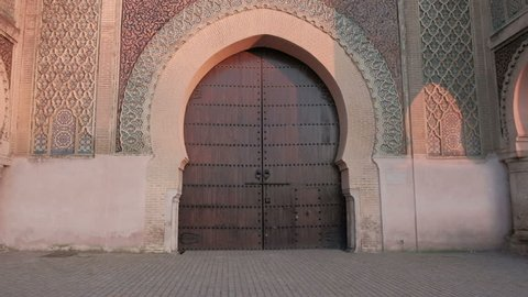 Meknes, Morocco - April 4, 2018: Camera tilt up view from door to top of Bab Mansour Gate in late afternoon
