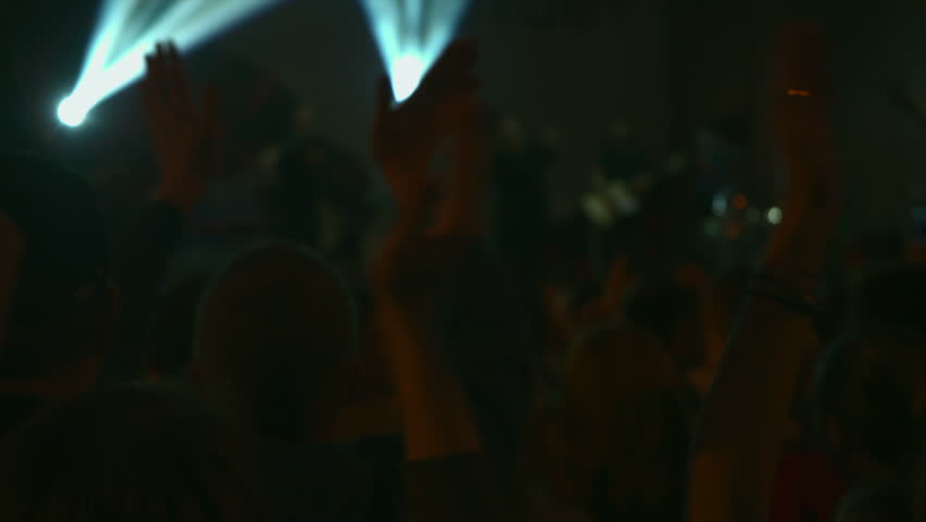 Footage of a crowd partying at a rock concert. Here is footage ot people crowd partying at ? concert or ? open air. There are dark silhouettes dancing jumping and waving hands. All space is full ot bl