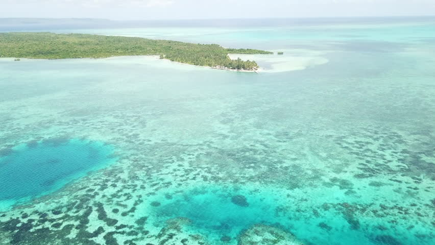 A remote island is surrounded by reefs in Wakatobi National Park in Indonesia. This region harbors extremely high marine biodiversity and is a popular destination for scuba diving and snorkeling.