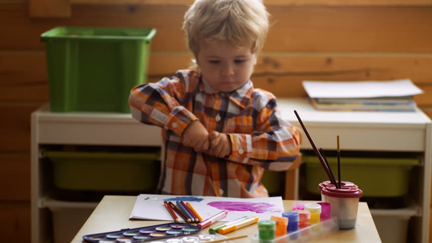Child drawing picture with paitint in album using a lot of painting tools. Creativity concept.