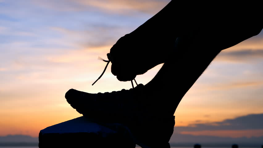 Running shoes - Man is tying shoe laces. male sport fitness runner getting ready for jogging outdoors the time during sunrise on dam road exercise. slow motion | Shutterstock HD Video #1013369627