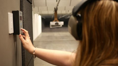 Woman uses a motorized slider to move a target closer at a indoor firing range