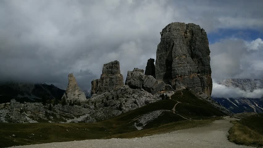 Time lapse of two hikers walinkg in front of the Cinque Torri (Five Towers) mountains in Cortina d'Ampezzo, Italy. Shot taken in the Dolomites.