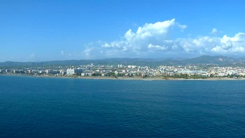 I'm flying on a parachute tied to a boat.  From a bird's-eye view you can see the sea, the beach and the city on the beach. There is a boat sailing on the sea. The analog of the flight on drone
