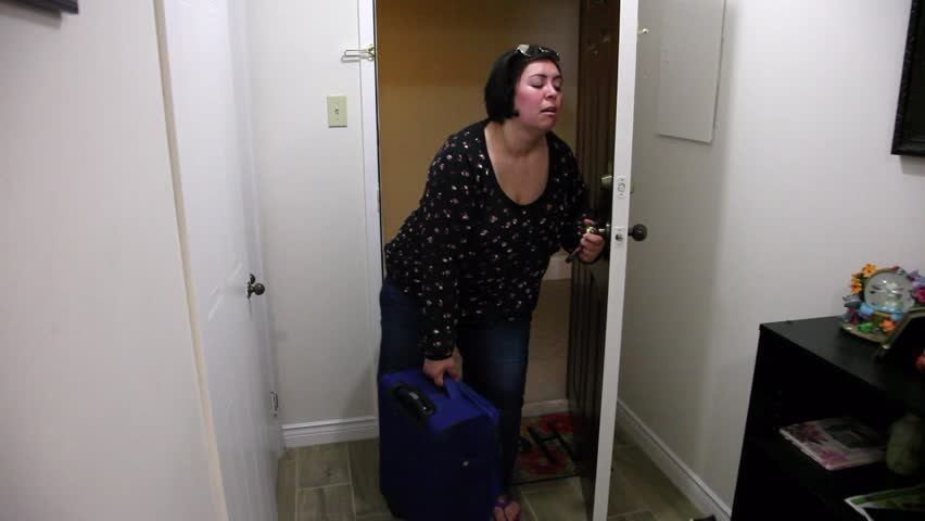 Woman returns Home from a trip. Exhasted.