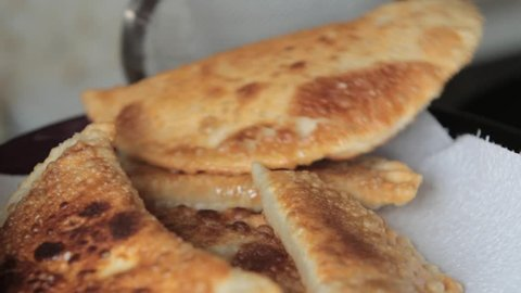 Housewife roasts chebureks in pan - Georgian national dish.cook prepares meat pies, working with the dough and filling, close-up.