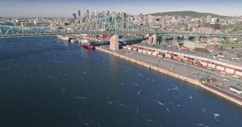 AERIAL: Flying over the railway, Pont Jacques-Cartier bridge, Saint Lawrence River and Montreal Skyline, Quebec, Canada